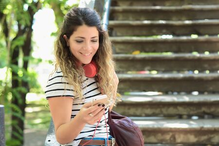 Beautiful urban woman sending message with smartphone on the street. Stock fotó