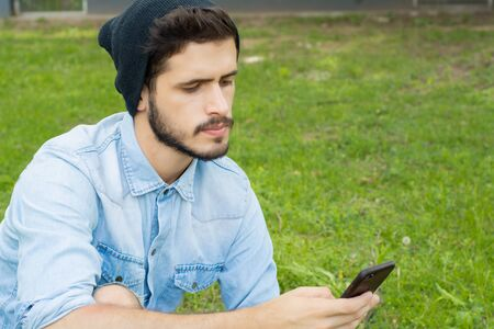 Portrait of young latin man using his smartphone. Outdoors.