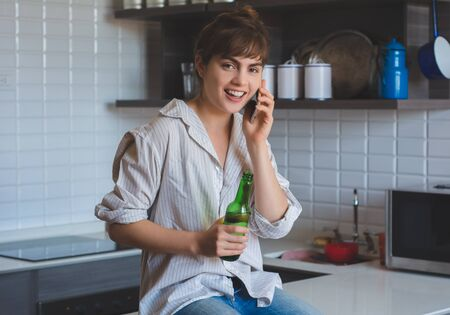 Young latin woman talking on mobile phone and drinks beer at home. Stock fotó