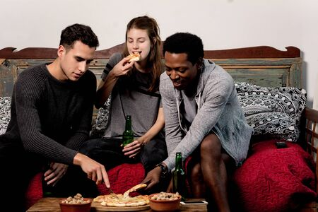 happy young friends eating pizza with beer on sofa at home.