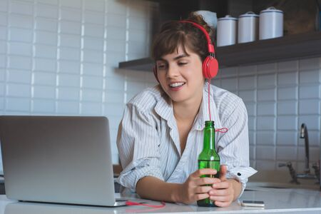 Young woman with beer and using her laptop pc in the kitchen at home.