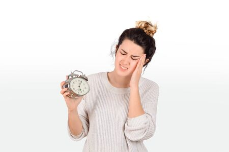 Young woman with alarm clock. Isolated over white background.