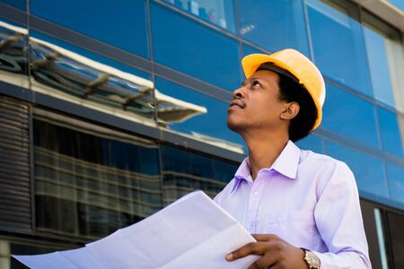 Professional architect in helmet looking away outside modern building. Stock fotó