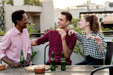 Group of young multi-ethnic friends with pizza and bottles of drink celebrating at outdoor rooftop. Friendship concept