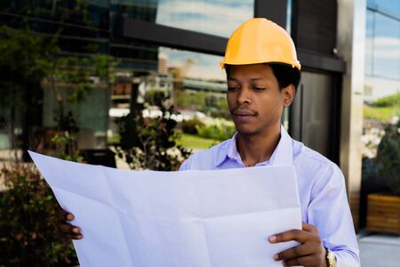 Portrait of Businessman engineer developer holding blueprint working outdoors.