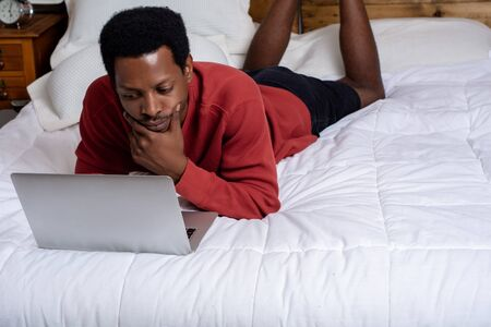 Young afro american man using his laptop in bed.