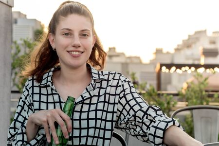 Young woman drinking at rooftop outdoor in urban city background, happy lifestyle. Stock fotó