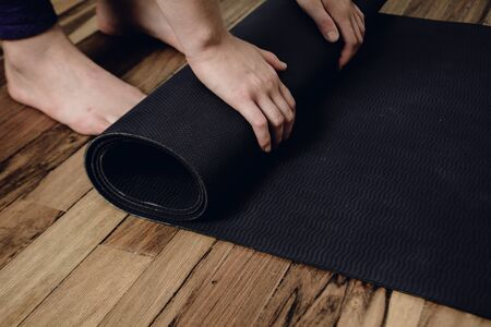 Close-up of attractive young woman rolling her fitness mat before or after yoga class at home. Healthy life concept.