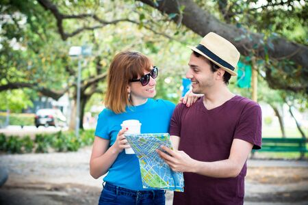 Young beautiful couple holding map in hands and traveling together. Tourism concept. Outdoors.
