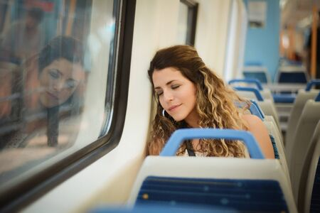 Young urban woman sleeping in a train travel beside the window. Modern people city lifestyle. Stock fotó