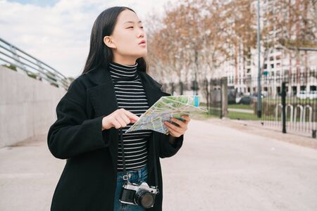 Portrait of young Asian woman holding a map and looking for directions outdoors in the street. Travel concept.