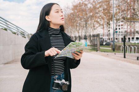Portret młodej azjatyckiej kobiety trzymającej mapę i szukającej kierunków na zewnątrz na ulicy. Koncepcja podróży.