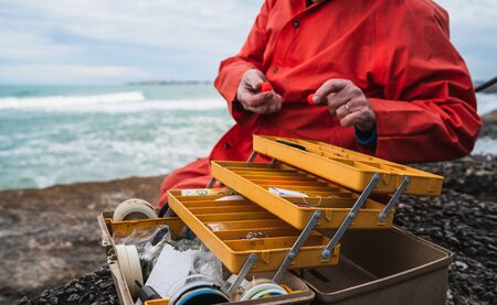 Close-up of a fisherman putting on bait with fishing equipment box. Fishing and sport concept.