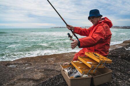 Portrait of an old man fishing in the sea. Fishing concept. Foto de archivo