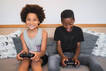Portrait of two Afro American brothers playing video games at home. Lifestyle and technology concept. Banque d'images