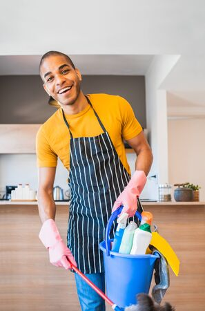 Portrait of young latin man holding a bucket with cleaning items at home. Housekeeping and cleaning concept.