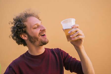 Portrait of young man enjoying and drinking beer against yellow background. Lifestyle concept. Reklamní fotografie
