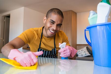 Close up of young latin man cleaning stains off the table at home. Housekeeping and cleaning concept.
