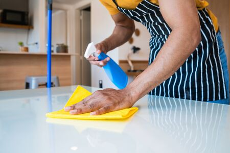 Close up of a man cleaning stains off the table at home. Housekeeping and cleaning concept. Stock fotó - 138293780