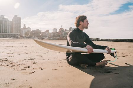Young surfer sitting on sandy beach looking at the ocean with his surfboard. Sport and water sport concept.