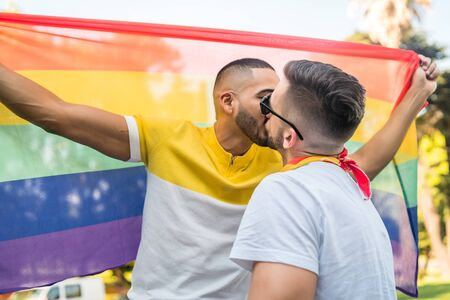 Portrait of young gay couple kissing and showing their love with rainbow flag in the stret. LGBT and love concept. Archivio Fotografico