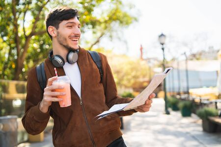 Portrait of young traveler man holding a map and looking for directions while drinking fresh fruit juice. Travel and holiday concept.