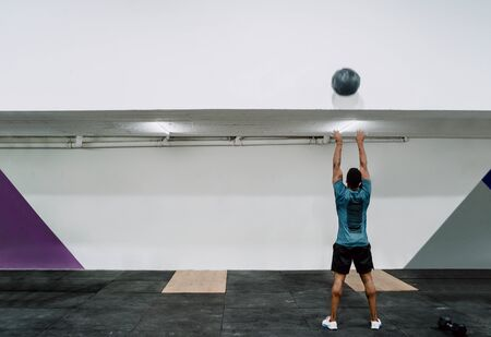 Portrait of young crossfit athlete doing exercise with ball at the gym. Crossfit, sport and healthy lifestyle concept.