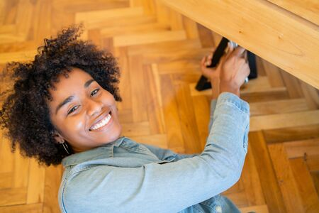 Portrait of young afro woman repairing furniture at home. Repair and renovation home concept.