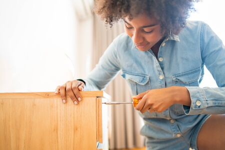 Portrait of young afro woman repairing furniture with a screwdriver at home. Repair and renovation home concept. Reklamní fotografie