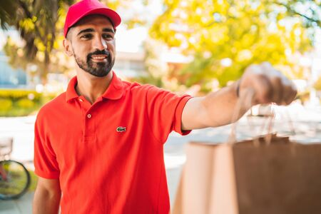 Portrait of a delivery man carrying packages while making home delivery to his customer. Delivery and shipping concept.