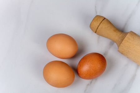 Close-up of some eggs with a rolling pin. Cooking concept.