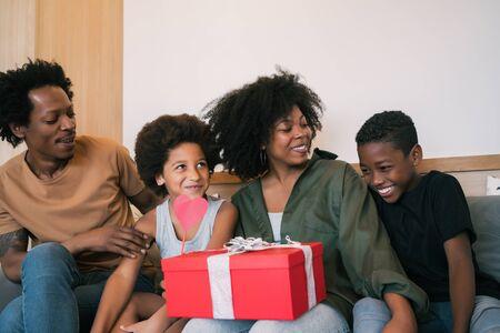 父亲和孩子们在母亲节祝贺母亲,并在家里给她礼物。母亲节庆祝理念。