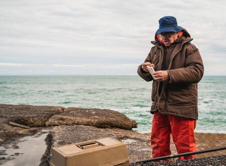 Portrait of a fisherman putting on bait with fishing equipment box. Fishing and sport concept.