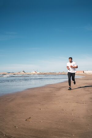 Portrait of an athletic man running at the beach. Sport, fitness and healthy lifestyle.