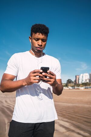 Portrait of an athletic man using his mobile phone on a break from training on the beach. Sport and health lifestyle.