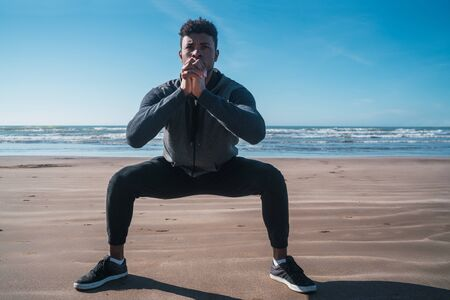 Portrait of an athletic man doing exercise at the beach. Sport and healthy lifestyle concept.