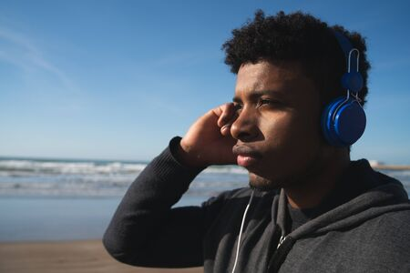 Portrait of an athletic man listening to music with earphones while resting for exercise at the beach. Sport and healthy lifestyle.