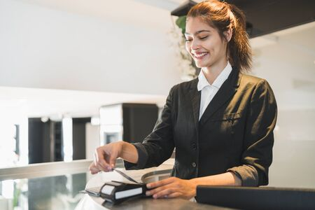 Portrait of receptionist passing card and charging guest stay at reception front desk. Travel concept.