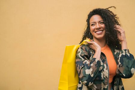 Portrait of young afro american latin woman holding shopping bags against yellow background. Shop and lifestyle concept.