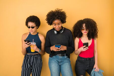 Portrait of three Afro friends using their mobile phone against yellow background. Friendship and lifestyle concept.