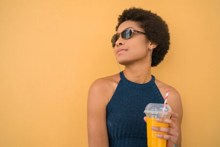 Portrait of young afro woman wearing summer clothes and drinking fresh fruit juice against yellow background. Lifestyle concept.