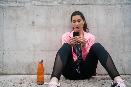 Portrait of an athletic woman using her mobile phone on a break from training against grey background. Sport and health lifestyle.