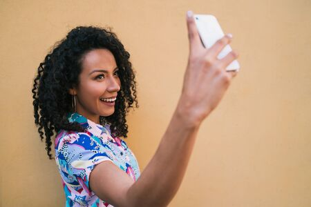Portrait of afro woman taking selfies with her mophile phone against yellow wall. Technology concept. Foto de archivo