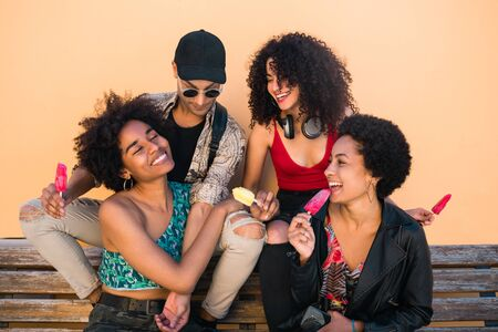 Portrait of multi-ethnic group of friends having fun and enjoying summertime while eating ice cream against yellow background.