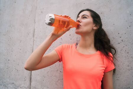 Portrait of an athletic woman drinking water after training against grey background. Sport and health lifestyle.