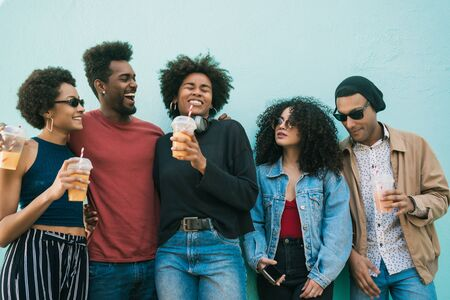 Portrait of afro friends having fun together and enjoying good time while drinking fresh fruit juice. Foto de archivo