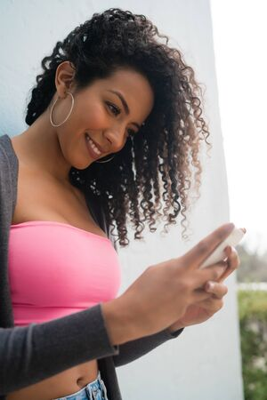 Portrait of young afro american latin woman using her mobile phone and sending messages. Communication concept. Foto de archivo