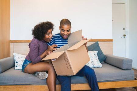 Portrait of happy young latin couple opening a package at home. Delivery, shipping and postal service concept. Buy online and stay at home. Covid-19 Quarantine.