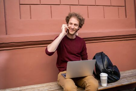 Portrait of young man talking on the phone and using his laptop while sitting outdoors. Technology and lifestyle concept.