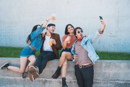 Portrait of a group of friends having fun together and enjoying good time while taking a selfie with mobile phone. Lifestyle and friendship concept.